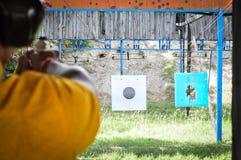 Tiro com a arma no alvo na escala de tiro fotografia de stock royalty free