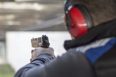 Tiro com a arma no alvo na escala de tiro Tiro da pistola do fogo praticando do homem Fotos de Stock Royalty Free