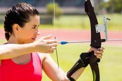 Tiro con l'arco di pratica dell'atleta femminile Fotografie Stock