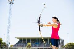 Tiro con l'arco di pratica dell'atleta femminile Fotografia Stock