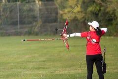 Tiro con l'arco di pratica dell'atleta femminile in stadio Fotografia Stock Libera da Diritti