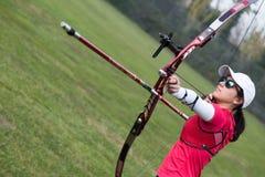 Tiro con l'arco di pratica dell'atleta femminile in stadio Immagine Stock Libera da Diritti