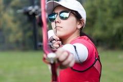 Tiro con l'arco di pratica dell'atleta femminile in stadio Fotografie Stock Libere da Diritti