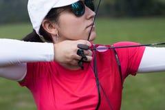 Tiro con l'arco di pratica dell'atleta femminile in stadio Immagini Stock Libere da Diritti
