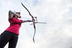Tiro con l'arco di pratica dell'atleta femminile in stadio Fotografia Stock