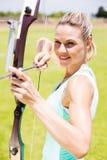 Tiro con l'arco di pratica felice dell'atleta femminile Fotografia Stock