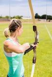 Tiro con l'arco di pratica felice dell'atleta femminile Immagine Stock