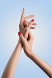 Tiro conceptual da mão bonita do ` s da mulher com verniz para as unhas do vermelho do tratamento de mãos Fotografia de Stock Royalty Free