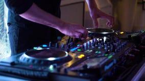 Tiro cosechado de DJ que trabaja en la estación de mezcla sana en luces que destellan del club almacen de metraje de vídeo