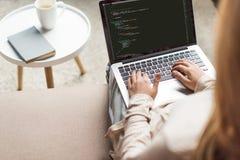 tiro cosechado de la codificación femenina joven del promotor con el ordenador portátil imágenes de archivo libres de regalías
