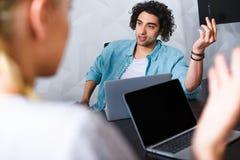 tiro cosechado de la empresaria en la tabla con los ordenadores portátiles y del hombre de negocios que gesticula a mano en moder imagenes de archivo