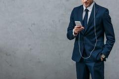 tiro cosechado de la música que escucha del hombre de negocios con los auriculares imagenes de archivo