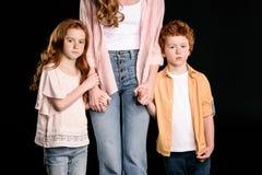 Tiro cosechado de la madre con los niños adorables del pelirrojo que se unen y que llevan a cabo las manos Imagen de archivo
