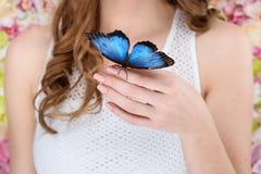 tiro cosechado de la mujer con la mariposa azul hermosa fotografía de archivo libre de regalías