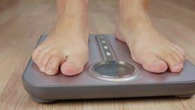 Tiro cosechado de la mujer descalza que controla su peso en escala almacen de video