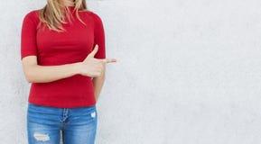 Tiro cosechado de la mujer en suéter rojo y los vaqueros de moda que se oponen a la pared blanca que señala en el espacio para su Imágenes de archivo libres de regalías
