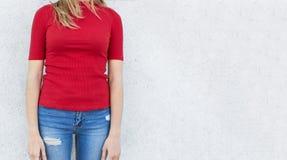 Tiro cosechado de la mujer joven que presenta contra la pared blanca del estudio, vestido en vaqueros de moda y suéter rojo con e Foto de archivo