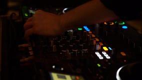 Tiro cosechado de las manos de DJ que mezclan música en mezclador en luces que destellan en club nocturno almacen de metraje de vídeo