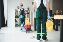tiro cosechado de los limpiadores jovenes que sostienen el diverso equipo de limpieza imagen de archivo libre de regalías