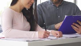 Tiro cosechado de los papeles de firma de una mujer con el vendedor en el salón del coche almacen de metraje de vídeo