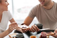 Tiro cosechado de los pares sonrientes que comen el desayuno por la mañana Foto de archivo