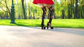 Tiro cosechado de los tacones altos que llevan de la mujer y de las danzas brillantes de las polainas en parque soleado metrajes