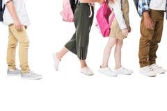 tiro cosechado de niños multiétnicos con las mochilas que se colocan junto aisladas en blanco fotografía de archivo
