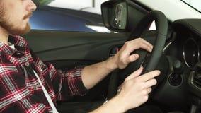 Tiro cosechado de un hombre barbudo que se sienta en un coche que sostiene el volante almacen de metraje de vídeo
