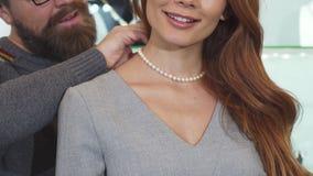 Tiro cosechado de un hombre que ajusta el collar de la perla en el cuello de su esposa almacen de video