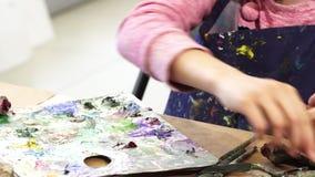 Tiro cosechado de una muchacha que exprime la pintura de un tubo encendido a una paleta
