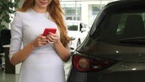 Tiro cosechado de una mujer alegre que usa el teléfono elegante que se coloca cerca de su coche almacen de metraje de vídeo