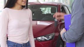 Tiro cosechado de una mujer feliz que recibe llaves del coche, sacudiendo las manos con el vendedor metrajes