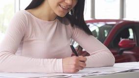 Tiro cosechado de una mujer que sonríe mientras que firma los papeles después de comprar un coche almacen de video
