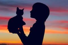 Tiro cosechado de una niña y de un gatito lindos en la puesta del sol Fotografía de archivo libre de regalías