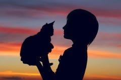 Tiro cosechado de una niña y de un gatito lindos en la puesta del sol Imagen de archivo
