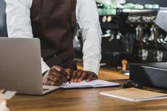 tiro cosechado del barista afroamericano joven que toma notas y que usa el ordenador portátil imágenes de archivo libres de regalías