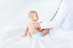 Tiro cosechado del bebé de examen del trabajador médico con el estetoscopio Fotos de archivo
