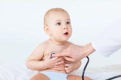 Tiro cosechado del bebé de examen del trabajador médico con el estetoscopio Foto de archivo