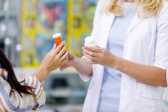 tiro cosechado del farmacéutico y del cliente que sostienen los envases con la medicación foto de archivo