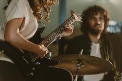 tiro cosechado del guitarrista femenino que realiza la canción con el batería borroso imágenes de archivo libres de regalías