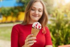Tiro cosechado del helado delicioso en manos del ` s de la muchacha La hembra joven se vistió en la ropa roja que sostenía el hel Imagen de archivo