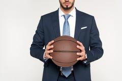 tiro cosechado del hombre de negocios joven que sostiene la bola del baloncesto Fotografía de archivo