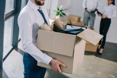 tiro cosechado del hombre de negocios que sostiene la caja de cartón mientras que vuelve a poner con los colegas foto de archivo