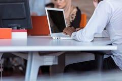 Tiro cosechado del teclado afroamericano del freelancer en el ordenador portátil mientras que trabaja en nuevo proyecto en casa imagen de archivo