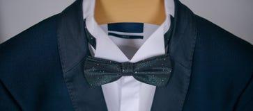 Tiro cosechado del traje elegante de los azules marinos con la camisa y la corbata de lazo blancas Imagenes de archivo