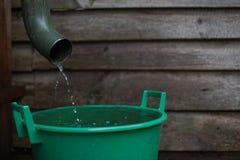 Tiro da água da chuva de uma calha em uma água que recolhe o reservatório imagens de stock