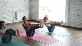 Tiro da bandeja das jovens senhoras que praticam a ioga que faz a pose de equilíbrio do barco na sala espaçoso clara As jovens mu filme