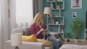 Tiro da bandeja da mulher que senta-se no sofá e em instruções de confecção de malhas de observação no telefone vídeos de arquivo