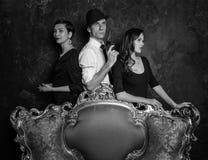 Tiro da história de detetive no estúdio Homem e duas mulheres Agente 007 Um homem em um chapéu com uma pistola e as duas mulheres fotos de stock royalty free