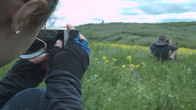 Tiro da jovem mulher em um homem do smartphone que toma imagens da natureza Os turistas fizeram uma parada no campo para fotograf filme